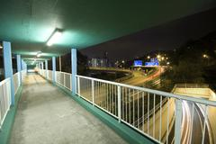 view on footbridge of modern urban city with freeway traffic at night - stock photo