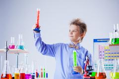 Handsome school boy posing with test-tubes in lab - stock photo