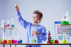 Cute boy posing with variety of reagents in lab - stock photo