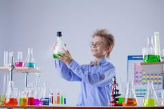Funny smiling boy holding flask with reagent - stock photo