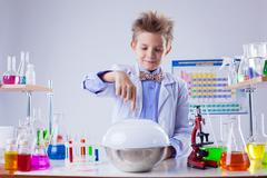 Smiling boy conducting experiment in chemistry lab - stock photo