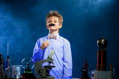 Cute school boy posing with fake mustache in lab - stock photo