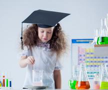 Cute curly-haired scientist stirs reagent in flask Stock Photos