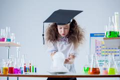 Stock Photo of Curious girl watching result of experiment in lab