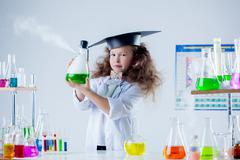 Pretty little brunette posing in chemistry lab - stock photo