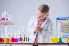 Image of little scientist posing with reagents - stock photo