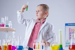 Cute boy looking at color of reagent in test-tube - stock photo