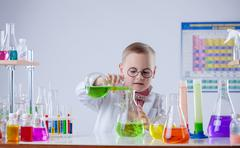 Funny young chemist pouring reagent into flask - stock photo