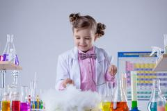 Smiling chemist successfully conducted experiment - stock photo