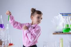 Attentive schoolgirl conducting experiment in lab Stock Photos