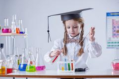 Image of smart girl mixing tubes in laboratory - stock photo
