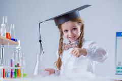Portrait of smiling schoolgirl in chemistry lab Stock Photos