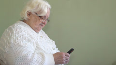 Old woman types short message on a mobile phone Stock Footage