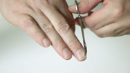 Stock Video Footage of Man trimming fingernails on right hand himself