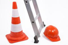 traffic cone, ladder and hardhat - stock photo