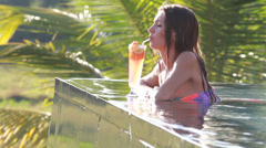Beautiful woman in swimming pool with cocktail Stock Footage