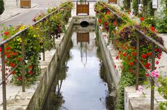 French waterway with hanging baskets and flowers Stock Photos