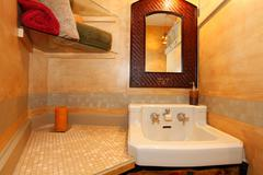 Antique sink with faux orange wall and mirror Stock Photos