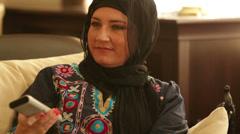 Muslim woman watching tv Stock Footage