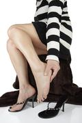 woman massaging aching feet over white background - stock photo