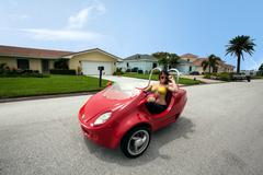 Young Brunette woman riding a Red Beach Car Stock Photos