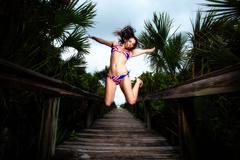 Young Brunette woman in a bikini on a beach boardwalk Stock Photos