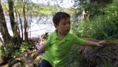 Little Asian Boy Points To Lake Or River, Then Climbs Over Log Toward Camera Stock Footage