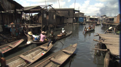 Canoes on busy waterway in Lagos slum. Stock Footage