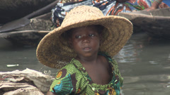 Child in large hat in canoe on slum water way Stock Footage