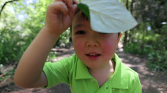 Silly Little Asian Boy Places A Big Leaf On His Head Stock Footage