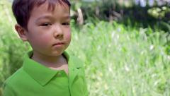 Multi-Ethnic Boy Stands In Tall Grass, Looks Away, Then Toward Camera And Smiles Stock Footage