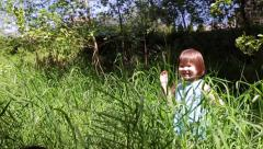 Excited Little Girl Hides In Tall Grass, Pops Up, Waves At Camera Stock Footage