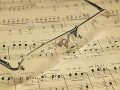 Glasses laying on score Stock Photos
