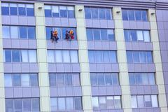 Two workers washing a skyscraper windows Stock Photos