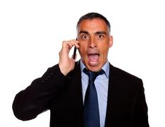 Surprised business man on cellphone Stock Photos