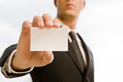 Man's hand showing business card. Black suit and tie. Stock Photos