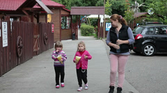 Mother and two little daughters walking an eating popcorn in amusement park Stock Footage