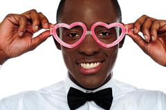 Smiling man wearing heart shaped eye-wear - stock photo