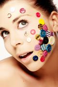Beautiful woman with buttons on her face - stock photo