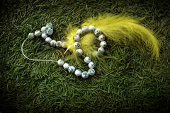 beads and yellow feather - stock photo