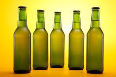 Chilled beer on yellow background - stock photo