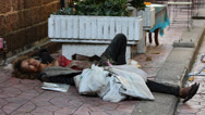 Stock Video Footage of Beggar woman sleeps on the street in central Bangkok on Khao San Road. Thailand