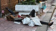 Beggar woman sleeps on the street in central Bangkok on Khao San Road. Thailand Stock Footage