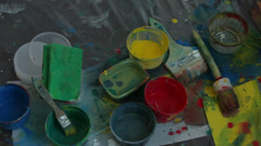 Paints and brushes lying on the floor Stock Footage