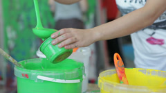 Man pours paint from bucket in container at the art studio. Stock Footage