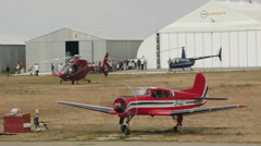 Yak-52 aircraft with the running engine parked with helicopter with working  Stock Footage