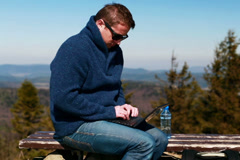 Man working on a laptop and sitting on a bench in the mountainous area Stock Footage