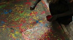 Women and men express themselves through paint on large canvases. Stock Footage