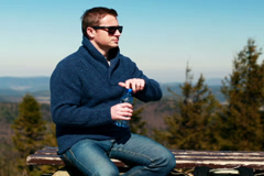 Man drinking water and sitting on a bench in the mountainous area Stock Footage