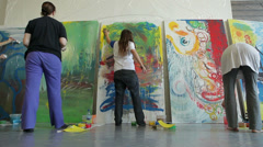People draw on huge canvases in studio. Dolly shot. Stock Footage